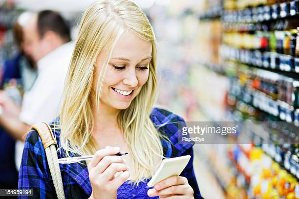 Pretty blonde smiles down at her shopping list in supermarket