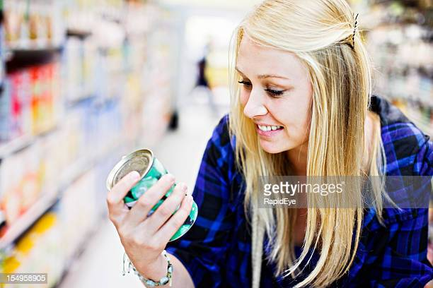 Pretty blonde smilingly checking canned goods in supermarket