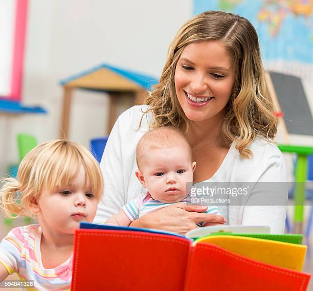 Pretty blonde teacher reading a book to two little girls