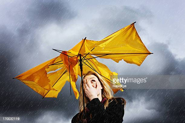 Pretty blonde with torn umbrella hides her face from storm