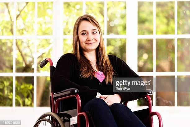 Schöne blonde Frau sitzt im Rollstuhl Lächeln tapfer