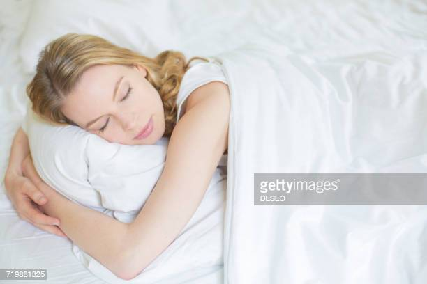 Pretty blonde woman sleeping in bed
