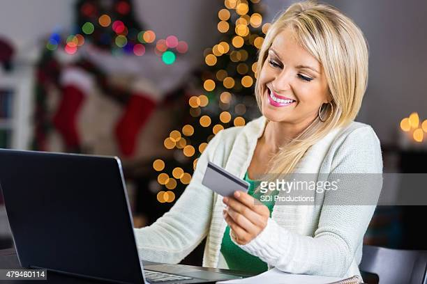 Pretty blonde woman using credit card for online Christmas shopping