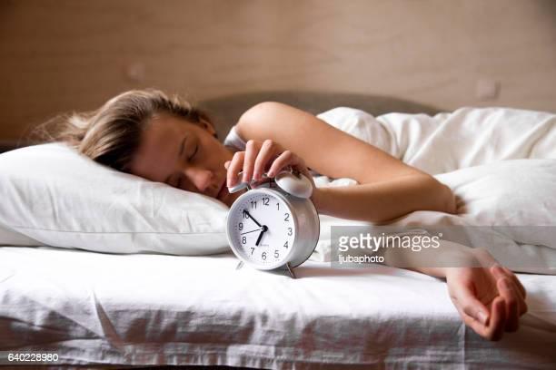 Jolie brunette étendant la main pour un radio-réveil