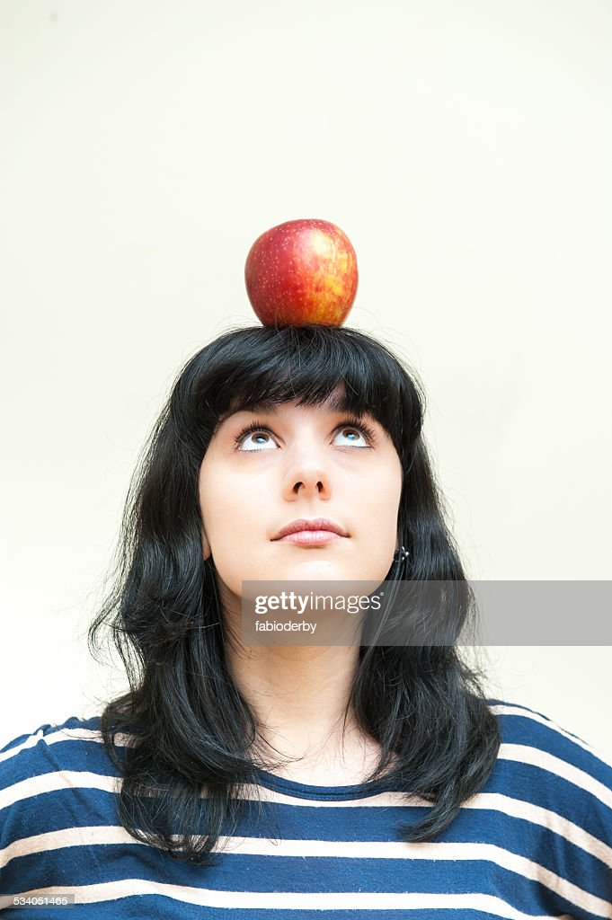 Pretty brunette girl looking red apple on head : Stock Photo