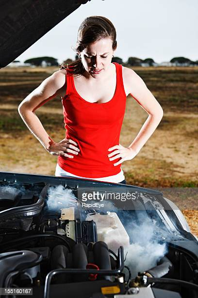 Pretty brunette looking into smoking car engine frustrated and worried