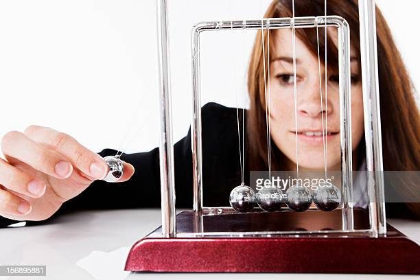 Pretty brunette playing with Newtons Cradle executive toy