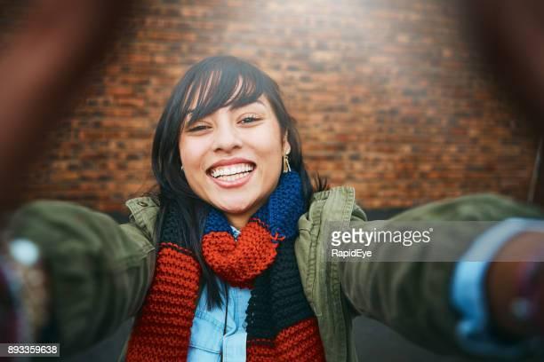 Pretty brunette takes smiling winter selfie