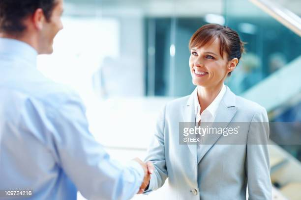 Pretty business woman shaking hands with man