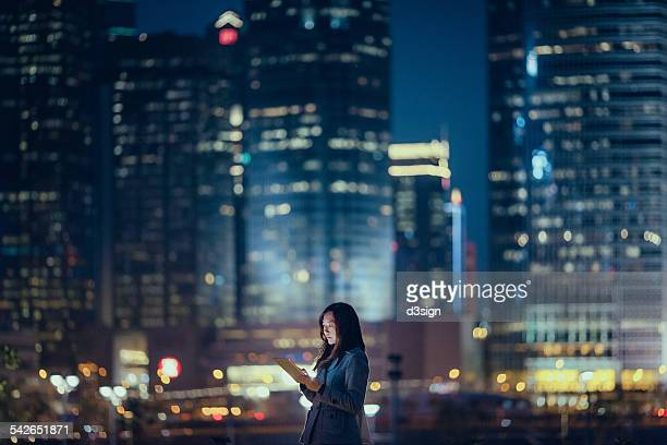 Pretty businesswoman using digital tablet in city