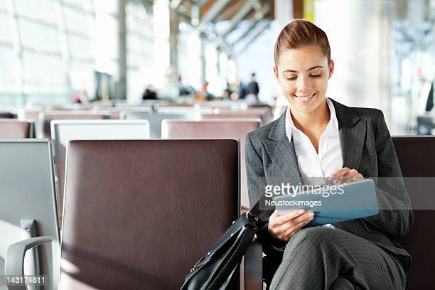 Pretty businesswoman with tablet in departure area