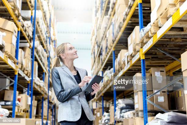 pretty businesswoman working at a warehouse - megastore stock photos and pictures