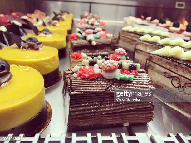 pretty cakes in a shop - yule log stock photos and pictures
