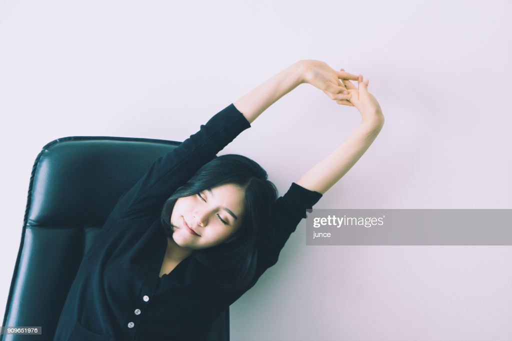 Pretty chinese office worker is stretching arm : Stock Photo