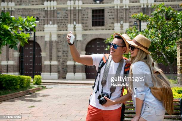 pretty couple doing tourism taking a selfie with a smartphone - hispanolistic stock photos and pictures