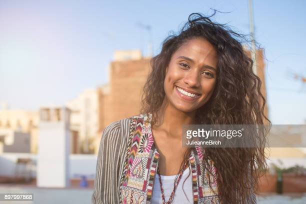 Pretty curly haired lady on rooftop terrace
