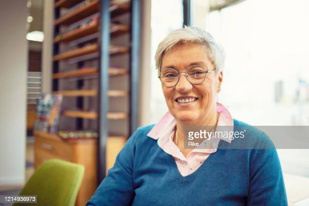 pretty customer with short silver hair is looking for new glasses from the optician - german short haired pointer stock pictures, royalty-free photos & images