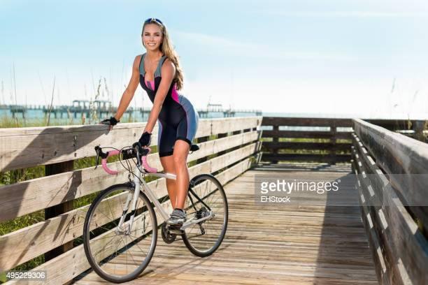 Pretty cyclist resting on boardwalk