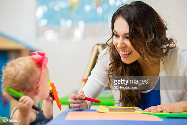 Pretty daycare teacher helps toddler with art project