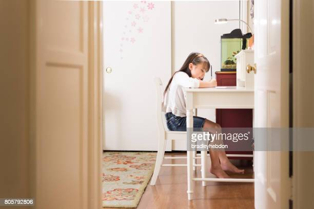 Pretty Eurasian girl doing homework in her bedroom