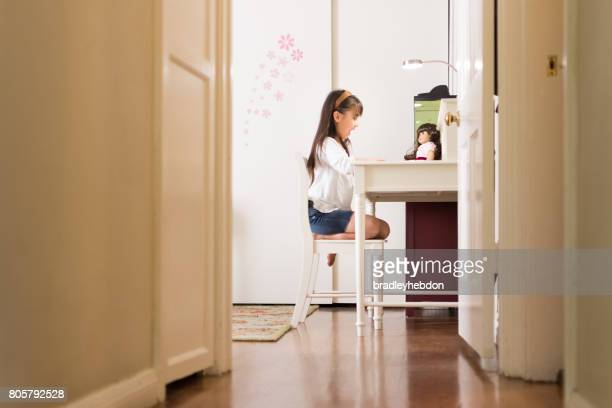 Pretty Eurasian girl reads book to doll in bedroom