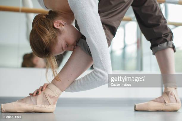 pretty female doing ballet exercise bowing to feet with pointe shoes - rehearsal stock pictures, royalty-free photos & images