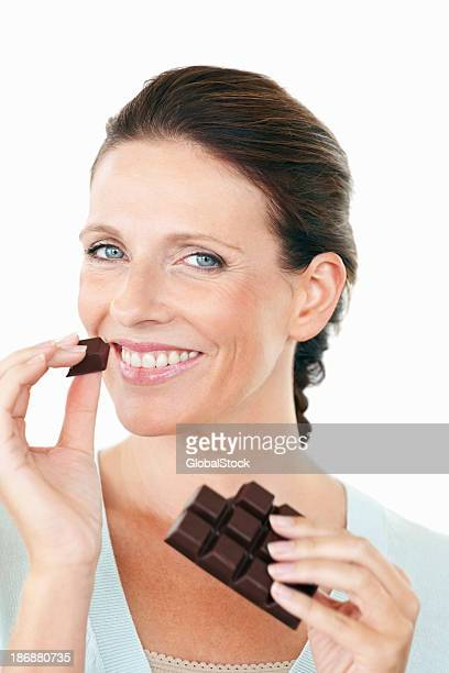 Pretty female eating a chocolate against white