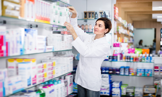 Pretty female pharmacist offering products 1132647798