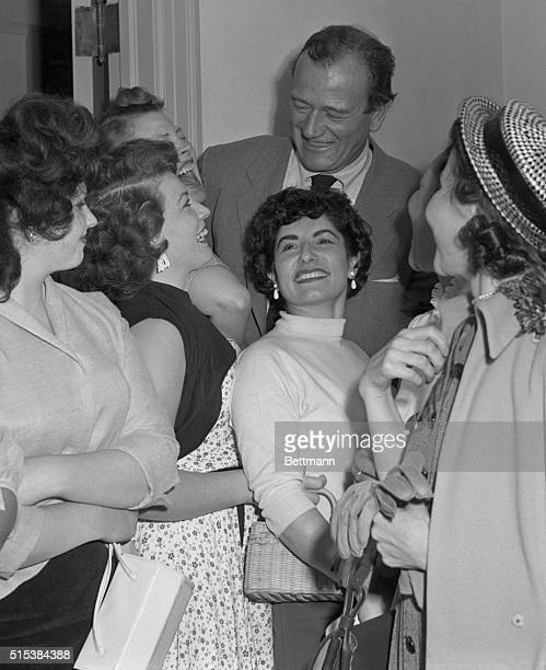 Pretty gals crowd around movie actor John Wayne as he leaves the court room in Los Angeles The lovely admirers were more interested in getting a...