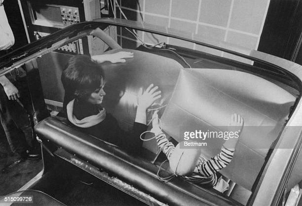 A pretty girl and a dummy of a child serve as the subjects in this demonstration of a new auto crash restraint system In this system a pillow is...