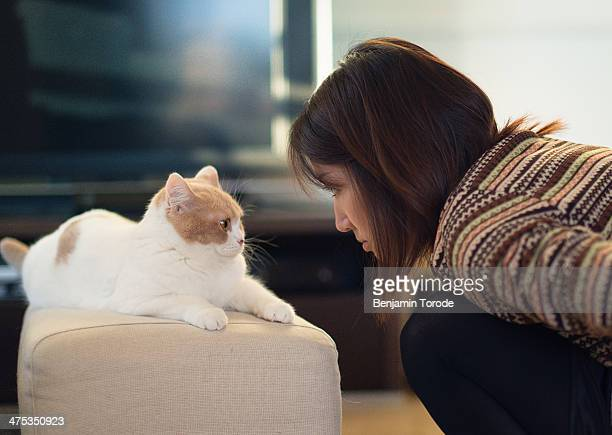 Pretty girl and white cat looking at one another