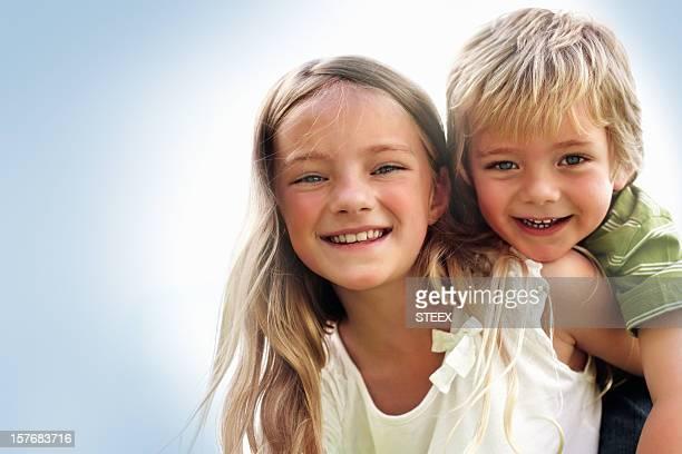 Bonita Menina transportar o seu irmão contra branco