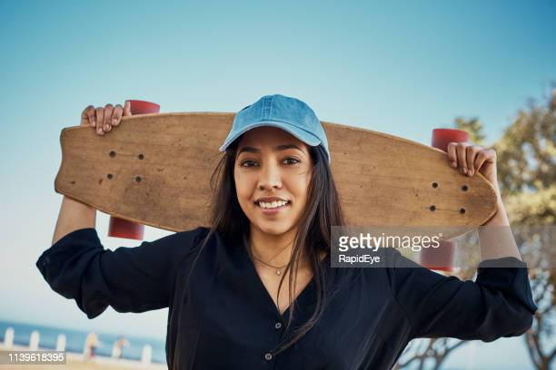 pretty girl carrying skateboard smiles happily at camera - tomboy stock photos and pictures