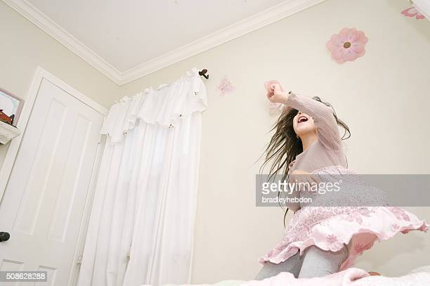 Pretty girl dancing on her bed with high energy