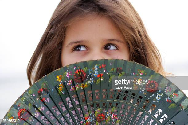 Pretty girl holding a Spanish fan in front of her face