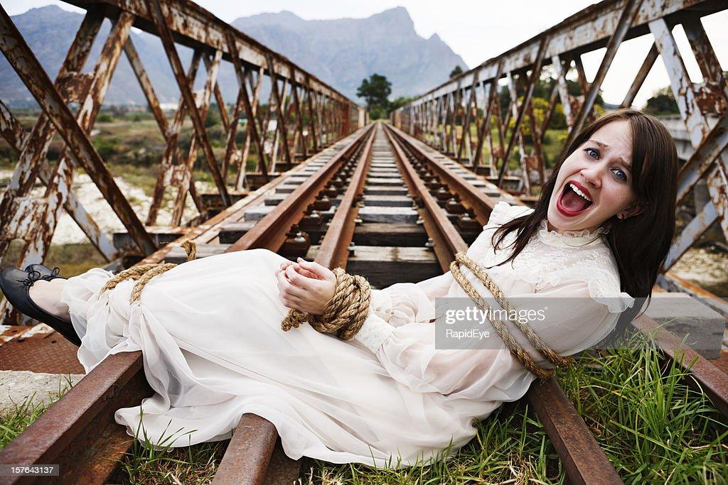 Pretty girl in period dress tied to railroad bridge, screaming : Stock Photo