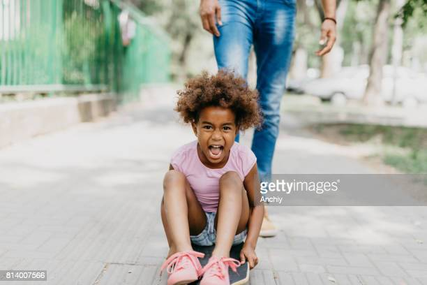 Pretty girl is screaming while sttting on the longboard
