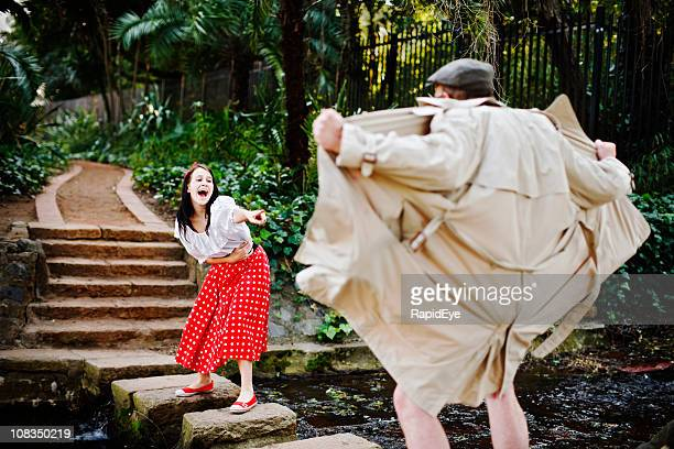 pretty girl laughs and points mockingly at flasher in park - female flasher stock pictures, royalty-free photos & images
