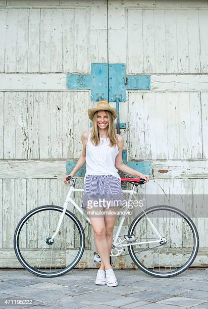 Pretty girl posing with a bicycle