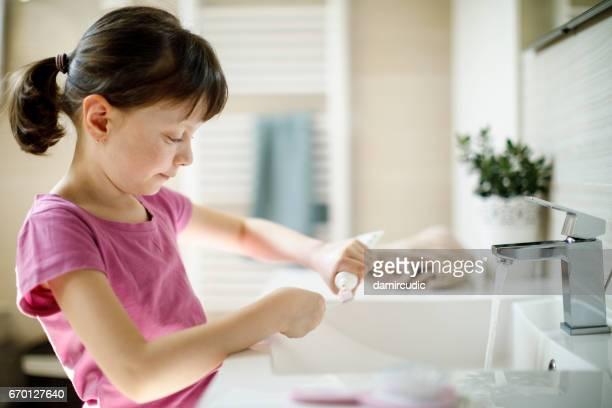 Hübsches Mädchen setzen eine Zahnpasta auf die Zahnbürste