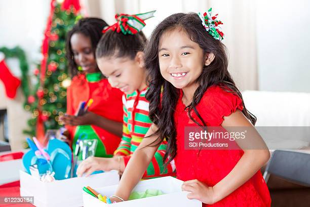 Pretty girl smiles while working on Christmas charity project