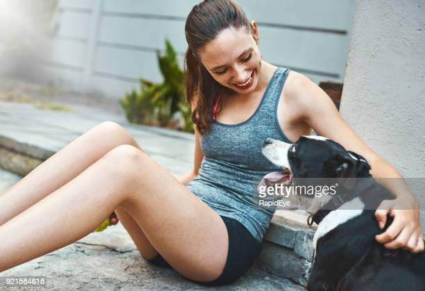 Pretty girl smiling down at happy pet dog