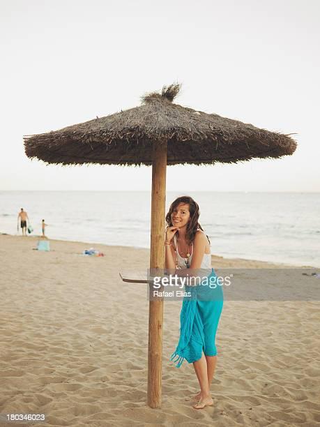 Pretty girl standing against a wood beach umbrella
