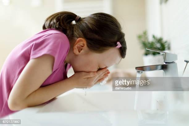 Pretty girl washing her face in bathroom