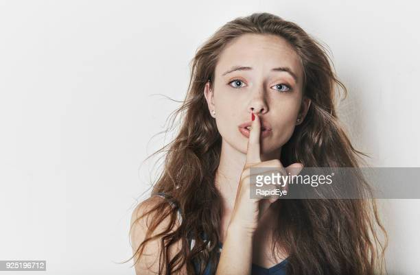 pretty girl with finger to lips - long nose stock photos and pictures