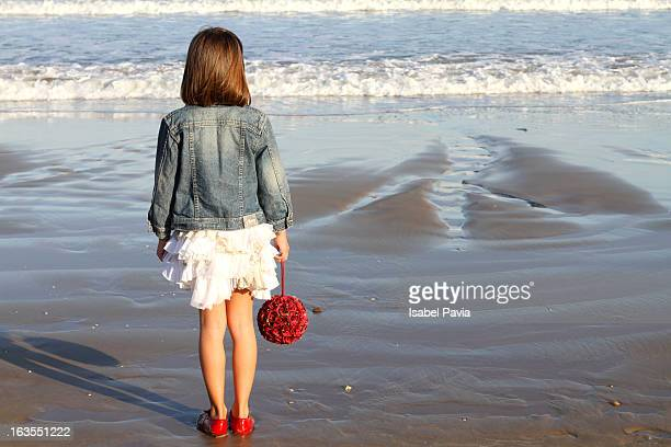 Pretty girl with red flowers looking at sea