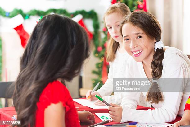 Pretty girl works on Christmas crafts with friends