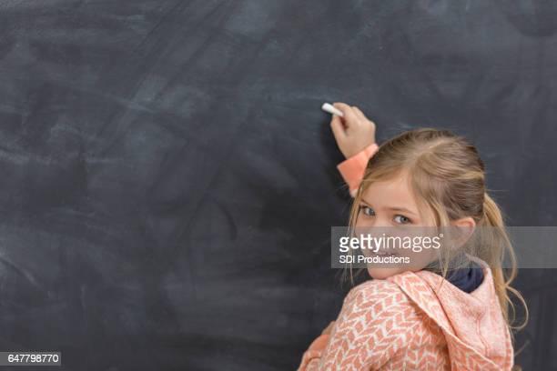 Pretty girl writes something on chalkboard at school