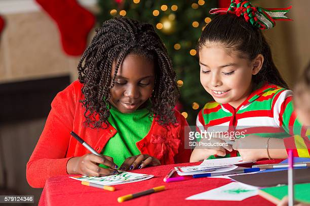 Pretty girls smiling as they write their letters to Santa