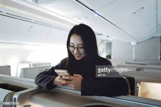 Pretty girls use mobile electronics in airplane cabins